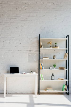 Photo for Home office with book shelf and laptop on table in sunlight - Royalty Free Image
