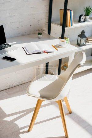 Photo pour Bureau à domicile avec smartphone, tasse à café et ordinateur portable sur la table au soleil - image libre de droit