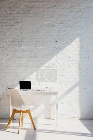 Photo pour Bureau à domicile avec ordinateur portable sur la table et la chaise près de la lumière du soleil - image libre de droit