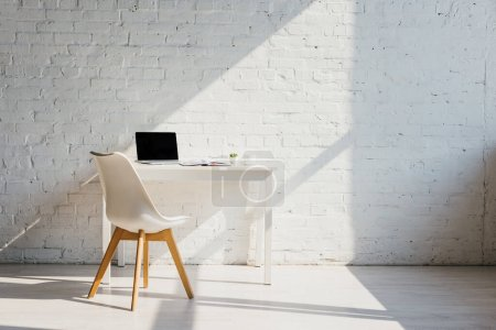 Photo for Home office with table, chair and laptop with blank screen in sunlight - Royalty Free Image