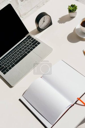 Photo for Empty workplace with laptop, clock, notepad and coffee in sunlight - Royalty Free Image