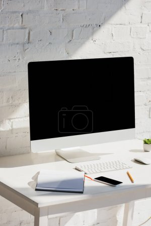 Photo pour Bureau à domicile avec écran d'ordinateur, clavier et souris sur la table avec smartphone - image libre de droit