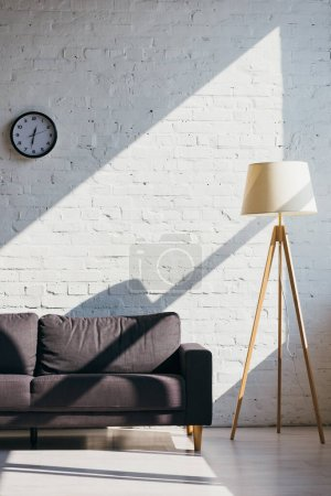 Photo for Living room with sofa, clock and lamp in sunlight - Royalty Free Image
