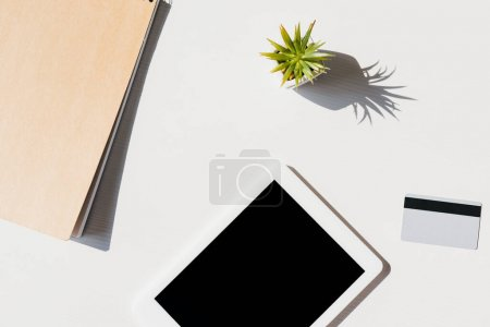Photo pour Vue du dessus du bloc-notes, succulent, carte de crédit et tablette numérique avec écran blanc - image libre de droit