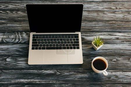 Photo pour Tasse de café, plante maison et ordinateur portable avec écran blanc sur la surface en bois sombre - image libre de droit