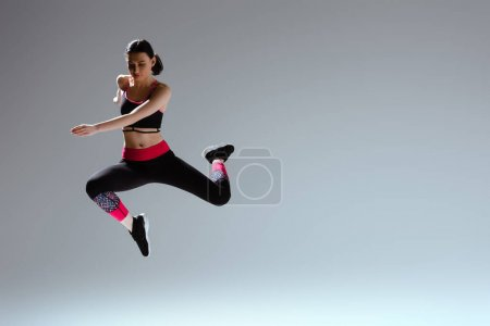 attractive woman in sportswear jumping on grey