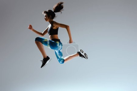 Photo for Side view of african american girl in sportswear jumping on grey - Royalty Free Image