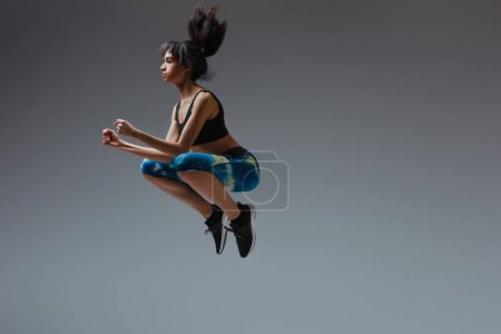 Photo for Sportive african american girl in sportswear jumping on grey - Royalty Free Image