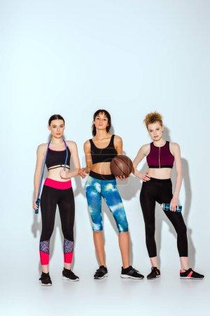 Photo pour Sportive afro-américaine fille tenant basket-ball et debout avec les jeunes femmes sur blanc - image libre de droit