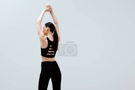 Photo for Woman in black sportswear standing with hands above head isolated on white - Royalty Free Image