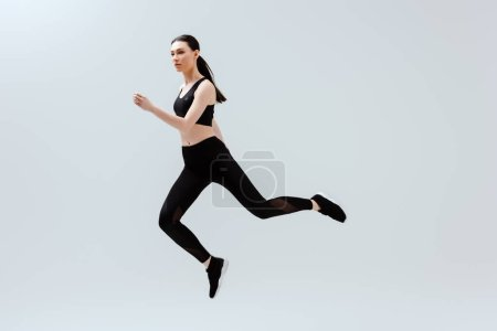 Photo for Pretty woman in black sportswear jumping isolated on white - Royalty Free Image