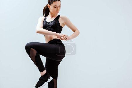 Photo pour Attrayant femme en noir sportswear exercice isolé sur blanc - image libre de droit