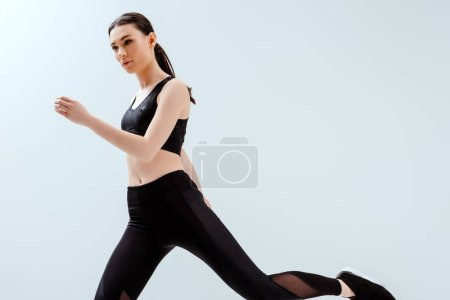 Photo for Beautiful woman in black sportswear exercising isolated on white - Royalty Free Image