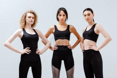 Photo pour Femmes multiculturelles en vêtements de sport debout avec les mains sur les hanches isolées sur blanc - image libre de droit
