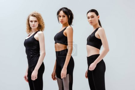 Photo for Beautiful and multicultural women in sportswear standing isolated on white - Royalty Free Image