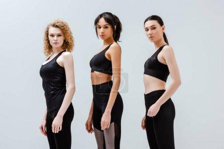 Photo pour Belles et multiculturelles femmes en vêtements de sport debout isolé sur blanc - image libre de droit