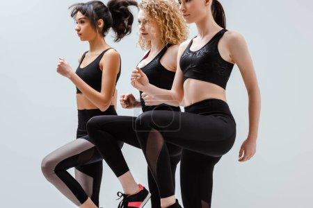 Photo pour Belles et multiculturelles femmes en vêtements de sport travailler isolé sur blanc - image libre de droit