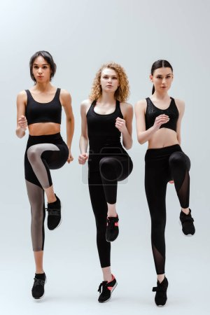Photo for Beautiful and multicultural women in sportswear exercising on white - Royalty Free Image