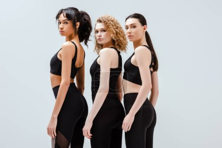 Photo pour Jolies et multiculturelles femmes en vêtements de sport debout isolé sur blanc - image libre de droit