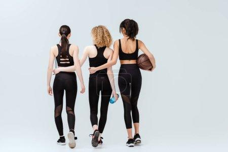 Photo pour Vue arrière de filles multiculturelles marchant avec des équipements sportifs sur blanc - image libre de droit