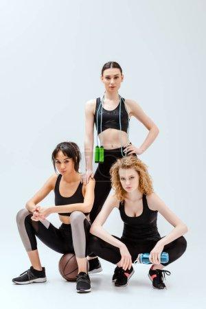 Photo pour Femmes multiculturelles posant avec des équipements sportifs sur blanc - image libre de droit