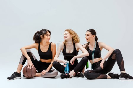 Photo for Happy multicultural girls sitting with sport equipment on white - Royalty Free Image
