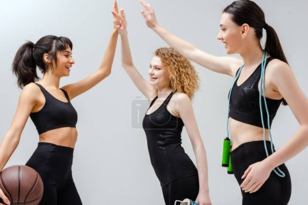 Photo for Happy multicultural girls in sportswear giving high five on white - Royalty Free Image