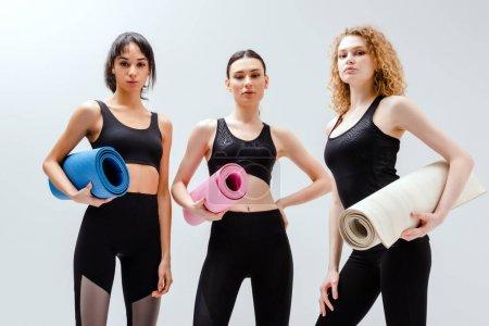 Photo pour Femmes sportives et multiculturelles tenant des tapis de fitness sur blanc - image libre de droit
