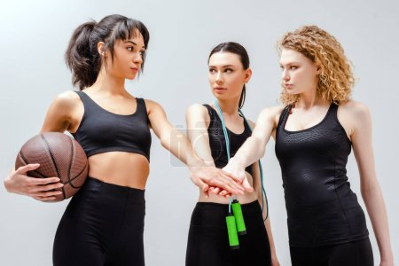 attractive multicultural girls in sportswear putting hands together on white