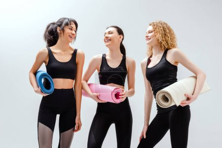 Photo for Happy and multicultural women holding fitness mats on white - Royalty Free Image