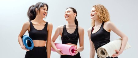Photo for Panoramic shot of happy and multicultural women holding fitness mats on white - Royalty Free Image