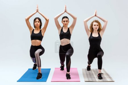 Photo for Attractive and multicultural women exercising on fitness mats isolated on white - Royalty Free Image