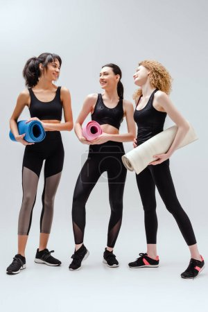 Photo for Cheerful and multicultural women holding fitness mats on white - Royalty Free Image