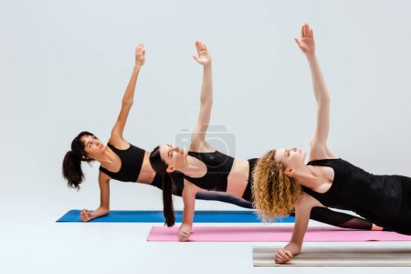 Photo for Multicultural women with outstretched hands training on fitness mats isolated on white - Royalty Free Image