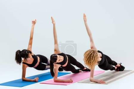 Photo for Multicultural women with outstretched hands exercising on fitness mats isolated on white - Royalty Free Image