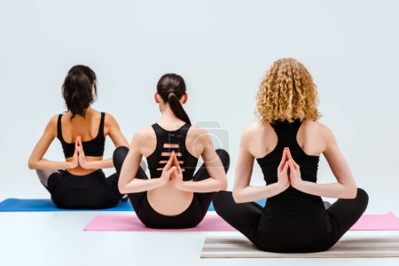 Photo for Back view of women in reverse prayer pose on yoga mats isolated on white - Royalty Free Image