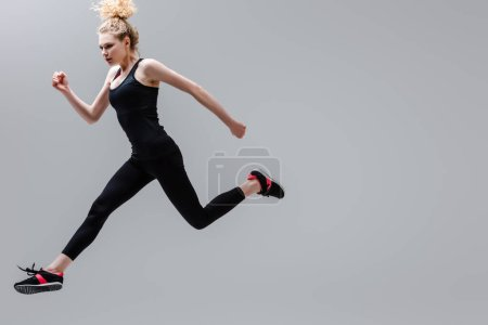 Photo for Young and curly sportswoman in sportswear jumping isolated on grey - Royalty Free Image