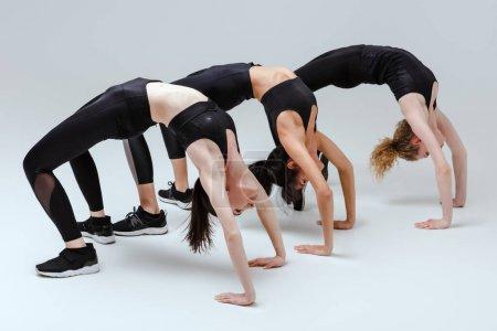 Photo pour Femmes multiculturelles faisant des exercices de bridge sur blanc - image libre de droit