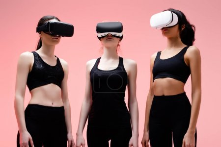 multicultural girls in sportswear and virtual reality headsets on pink