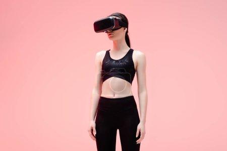 Photo pour Jeune sportive en réalité virtuelle casque debout sur rose - image libre de droit