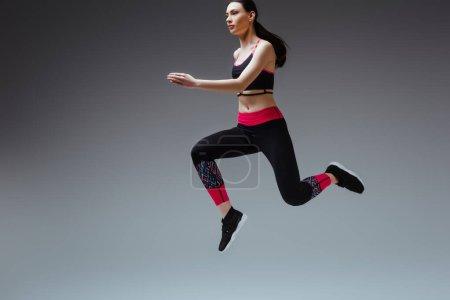 Photo pour Jeune et jolie femme en tenue de sport sautant sur gris - image libre de droit