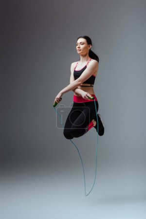 Photo for Pretty woman in sportswear jumping with skipping rope on grey - Royalty Free Image