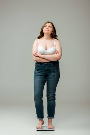 Photo for Plus size woman in jeans and bra standing with crossed arms on scales and looking up on grey - Royalty Free Image