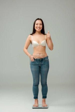 Foto de Feliz sobrepeso asiático mujer de pie en escalas y mostrando el pulgar hacia arriba en gris - Imagen libre de derechos