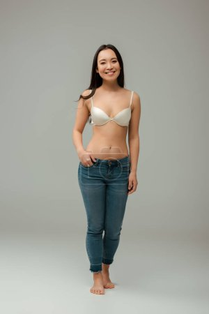 Photo for Happy overweight asian woman standing with hand in pocket on grey - Royalty Free Image