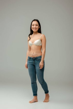 happy overweight asian girl standing on grey