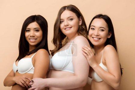 Foto de Mujeres multiculturales sonrientes y con sobrepeso en sostenes aislados en beige - Imagen libre de derechos
