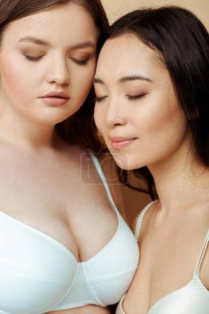 Foto de Hermosa mujer con sobrepeso y chica asiática con los ojos cerrados aislados en beige, cuerpo concepto positivo - Imagen libre de derechos