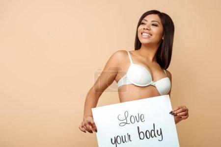 Photo pour Heureuse femme afro-américaine tenant la pancarte avec amour votre lettrage de corps isolé sur beige - image libre de droit