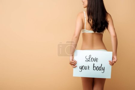 Photo for Cropped view of happy girl holding placard with love your body lettering isolated on beige - Royalty Free Image